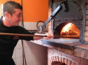 CHEF LEO slides a pizza into the oven. (Staff Photo)