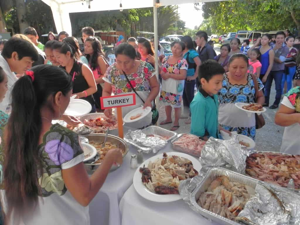 MAYAN VILLAGERS line up for turkey feast in Paamul as Thanksgiving guests. (Staff Photo)